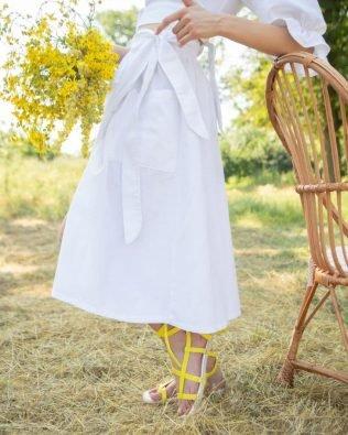 Белая юбка из льна с запахом и карманами ниже колена